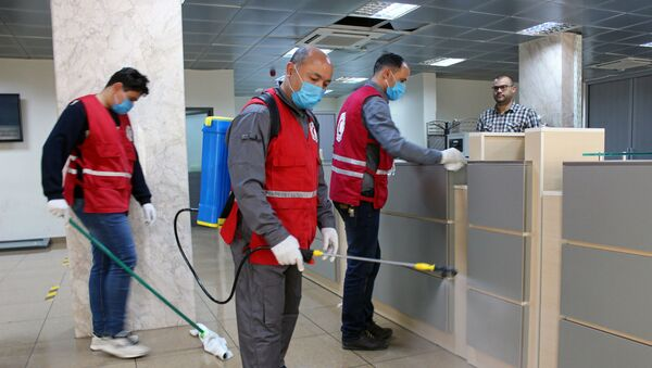 Members of Red Crescent spray disinfectants, as part of precautionary measures against coronavirus disease (COVID-19) at government offices in Misrata, Libya March 21, 2020. Picture taken March 21, 2020 - Sputnik International