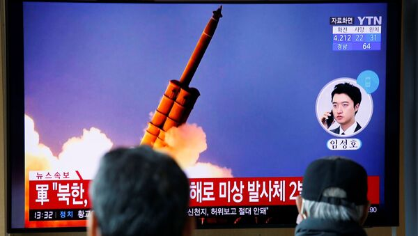 People watch a TV showing a file picture for a news report on North Korea firing two unidentified projectiles, in Seoul, South Korea, March 2, 2020. - Sputnik International