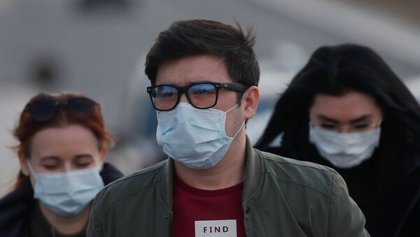People wearing protective masks walk near a hospital for patients infected with coronavirus disease (COVID-19) on the outskirts of Moscow, Russia March 23, 2020. - Sputnik International