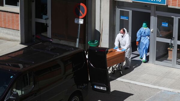 A funeral worker wearing a protective suit carries a coffin out of the morgue at Severo Ochoa Hospital, during the coronavirus disease (COVID-19) outbreak in Leganes, Spain, March 26, 2020 - Sputnik International