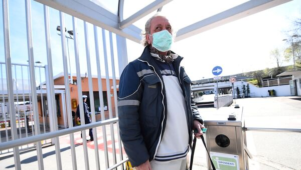 Fiat Chrysler Automobiles (FCA) worker, wearing a protective face mask, leaves a Mirafiori plant, after the Italian government puts the whole country on lockdown as new coronavirus cases surge, in Turin, Italy March 10, 2020 - Sputnik International