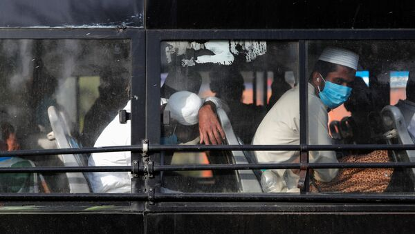 Men wearing protective masks sit inside a bus that will take them to a quarantine facility, amid concerns about the spread of coronavirus disease (COVID-19), in Nizamuddin area of New Delhi, India, March 31, 2020 - Sputnik International
