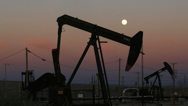 FILE - In this June 8, 2017, file photo, oil derricks are busy pumping as the moon rises near the La Paloma Generating Station in McKittrick, Calif. The U.S. is on pace to leapfrog both Saudi Arabia and Russia as the world's biggest oil producer - Sputnik International