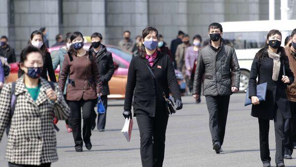 Pedestrians wear face masks to help prevent the spread of the coronavirus, Wednesday, 1 April 2020, in Pyongyang, North Korea.  - Sputnik International