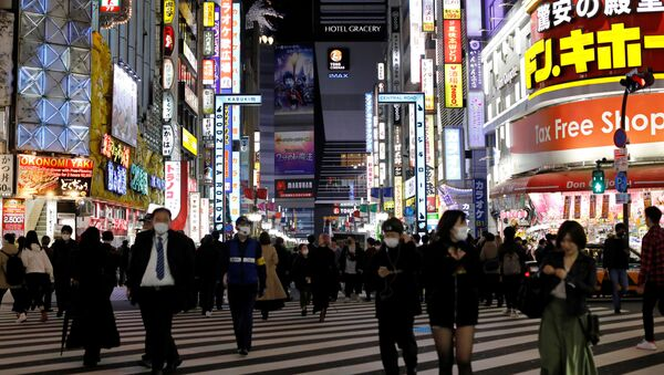 Passersby wearing protective face masks, following an outbreak of the coronavirus disease (COVID-19), walk at Kabukicho entertainment and shopping district in Tokyo, Japan - Sputnik International