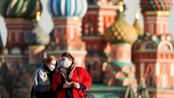 Women with protective masks, widely used as a preventive measure against coronavirus disease (COVID-19), walk across Red Square near the St. Basil's Cathedral in central Moscow, Russia March 26, 2020 - Sputnik International