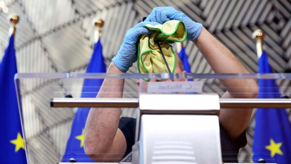 A man disinfects a desk before a news conference of European Council President Charles Michel after after EU heads of state held a videoconference to discuss measures for the coronavirus disease (COVID-19) in Brussels, Belgium, March 26, 2020.  - Sputnik International