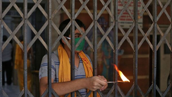 A Hindu priest performs a ritual known as Aarti to bless the devotees (not pictured) on the occasion of Ramnavmi festival at a temple during a 21-day nationwide lockdown to slow the spreading of coronavirus disease (COVID-19) in in Mumbai, India, April 2, 2020. - Sputnik International