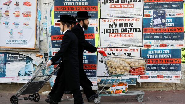 Ultra-Orthodox Jewish men push trolleys as they pass by billboards urging people to stay in their homes and keeping with government restrictions amid coronavirus disease (COVID-19) in Ashdod, Israel  April 1, 2020 - Sputnik International