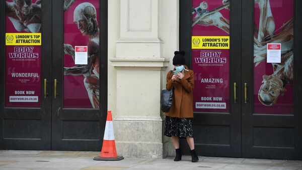 A woman looks at her phone whilst wearing a mask in Shaftesbury Avenue as the spread of the coronavirus disease (COVID-19) continues, London, Britain, March 31, 2020 - Sputnik International