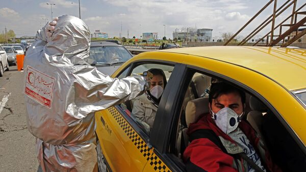 Members of the Iranian Red Crescent test people for coronavirus Covid-19 symptoms, as police blocked Tehran to Alborz highway to check every car following orders by the Iranian government, outside Tehran on March 26, 2020 - Sputnik International
