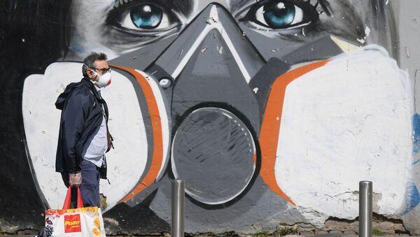 A man wearing a face mask walks past a graffiti - Sputnik International
