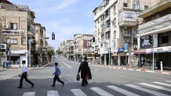 An Ultra orthodox man crosses a street in the city of Bnei Brak, a Tel Aviv suburb, Israel, Thursday, April 2, 2020. On Wednesday, Netanyahu ordered a police cordon around the largely ultra-Orthodox city of Bnei Brak, east of Tel Aviv, to limit movement to and from the city. Bnei Brak has the second highest number of coronavirus cases in Israel. - Sputnik International
