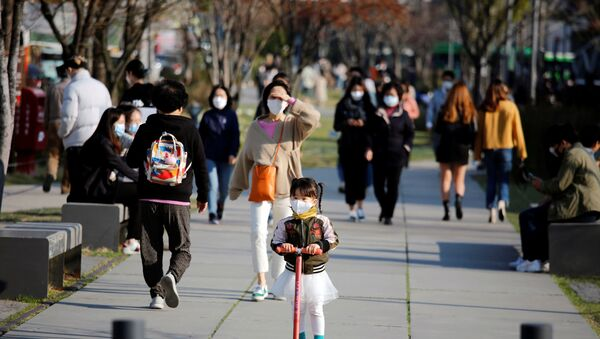 A girl wearing a protective face mask to prevent contracting the coronavirus disease (COVID-19) rides a toy kick scooter at a park in Seoul, South Korea, April 3, 2020 - Sputnik International