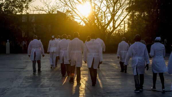 A brigade of health professionals, who volunteered to travel to the West Indies, walk back to their campus after posing for news photographers, in Havana, Cuba, Saturday, March 28, 2020. The medical teams will travel on Saturday to the dual-island country Saint Kitts and Nevis, to assist local authorities with an upsurge of COVID-19 cases. - Sputnik International