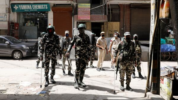 Paramilitary personnel and police officers stand guard on the street as India ordered a 21-day nationwide lockdown to limit the spreading of coronavirus disease (COVID-19), in New Delhi, India, March 25, 2020 - Sputnik International