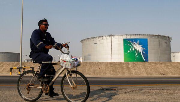 An employee rides a bicycle next to oil tanks at Saudi Aramco oil facility in Abqaiq, Saudi Arabia October 12, 2019.  - Sputnik International
