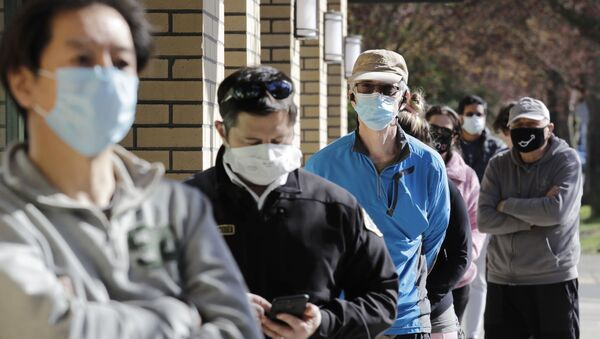 Customers wear a variety of protective masks as they wait some six-feet apart to enter a Trader Joe's store, where the number of customers allowed inside at any one time was limited because of the coronavirus outbreak, Wednesday, April 8, 2020, in Seattle - Sputnik International