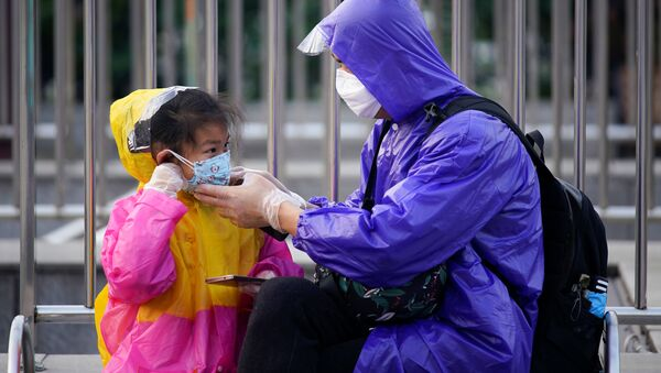 A person helps a child put on a protective face mask at Wuhan's Hankou Railway Station - Sputnik International