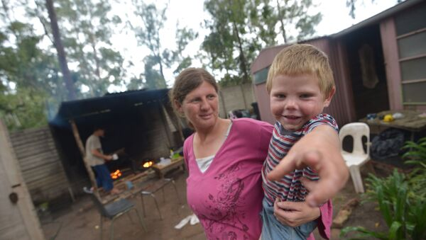 Marinda Labuschagne and her boy stand in front of their home with her husband cooking in the kitchen on a wood fire at a squatter camp for poor white South Africans at Coronation Park in Krugersdorp, on December 12, 2013 - Sputnik International