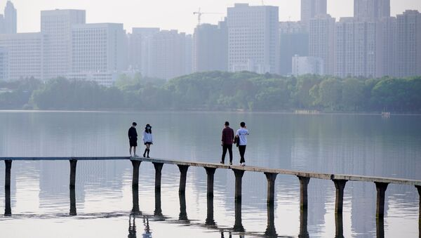 People wearing face masks, walk along the East Lake after lockdown in Wuhan, the epicentre of China's novel coronavirus disease (COVID-19) outbreak, is lifted, in Wuhan, Hubei province, China, April 9, 2020 - Sputnik International