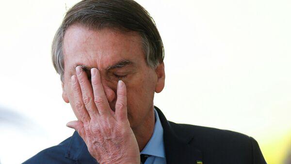 Brazil's President Jair Bolsonaro reacts while meeting supporters as he leaves Alvorada Palace, amid the coronavirus disease (COVID-19) outbreak, in Brasilia, Brazil, April 9, 2020. - Sputnik International