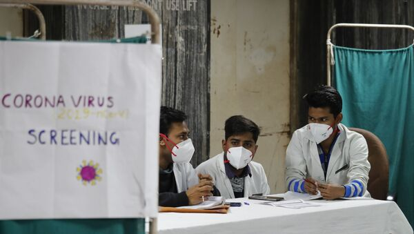 Indian doctors wait in an area set aside for possible COVID-19 patients at a free screening camp at a government run homeopathic hospital in New Delhi, India, Friday, March 13, 2020 - Sputnik International