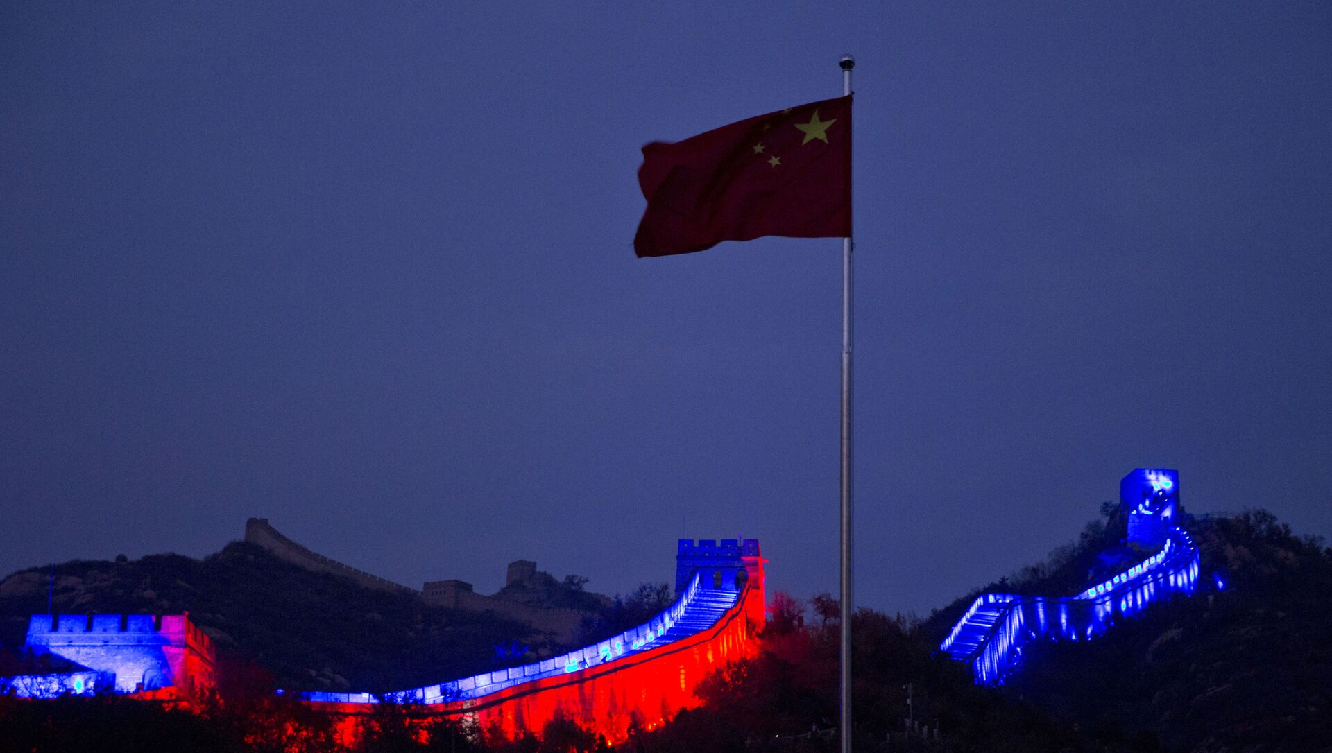 The Chinese national flag flies near a section of the Great Wall of China prepared to be lit by blue light to commemorate the 70th anniversary of the United Nations on the outskirts of Beijing, China, Saturday, Oct. 24, 2015. More than 200 iconic monuments, buildings, museums, bridges and other landmarks around the world were lighted up with blue - the official color of the United Nations to mark its 70th anniversary. - Sputnik International, 1920, 09.04.2021