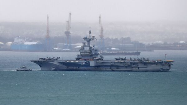 A picture taken on March 13, 2020, shows the French aircraft carrier Charles de Gaulle as it enters the port of Brest, in western France.  - Sputnik International