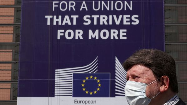 FILE PHOTO: A man wearing a face mask walks past the European Commission headquarters as the spread of coronavirus disease (COVID-19) continues in Brussels, Belgium April 9, 2020.  - Sputnik International