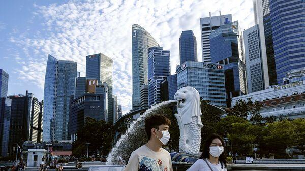 Пара в масках у статуи Мерлиона в Сингапуре - Sputnik International