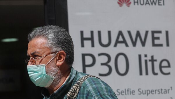 A man, wearing a protective mask due to the spread of coronavirus disease (COVID-19), walks past a Huawei store in Cairo, Egypt March 31, 2020. - Sputnik International