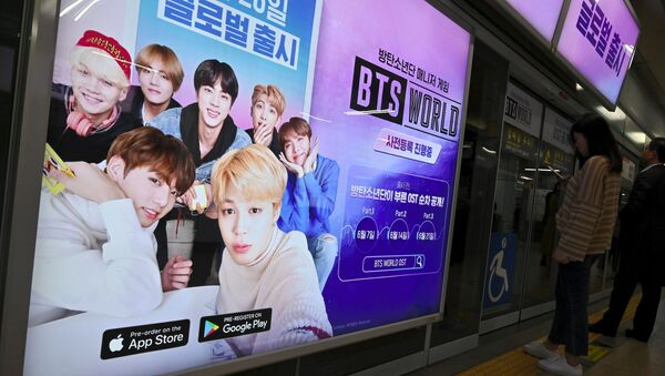 Passengers stand next to an advertisement for the role-playing game BTS World at a subway station in Seoul on June 25, 2019. - Sputnik International