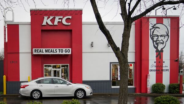 A vehicle waits at the drive-thru window of a Kentucky Fried Chicken (KFC) after a state mandated carry-out only policy went into effect in order to slow the spread of the novel coronavirus (COVID-19) in Louisville, Ky, U.S. March 24, 2020.  - Sputnik International