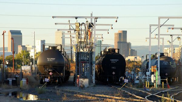 Oil tanker railcars are parked at a filling rack at sunrise with the Denver downtown skyline in the background October 14, 2014 - Sputnik International