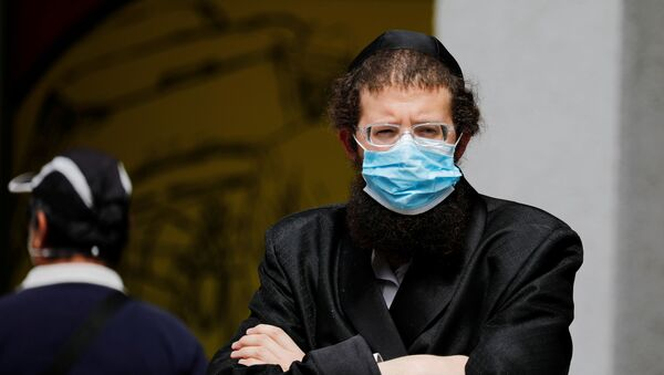 An ultra-Orthodox Jewish man wearing a mask looks on in Bnei Brak, a town badly affected by the coronavirus disease (COVID-19), and which Israel declared a restricted zone due to its high rate of infections, near Tel Aviv, Israel April 5, 2020 - Sputnik International