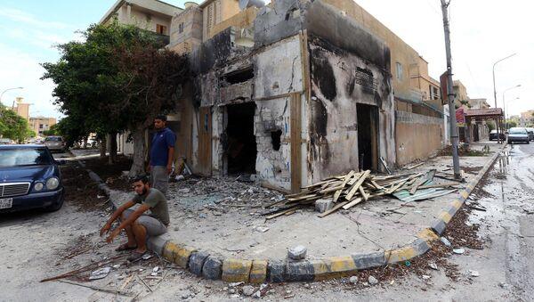 Libyans sit next to a damaged hosue in Sabratha - Sputnik International