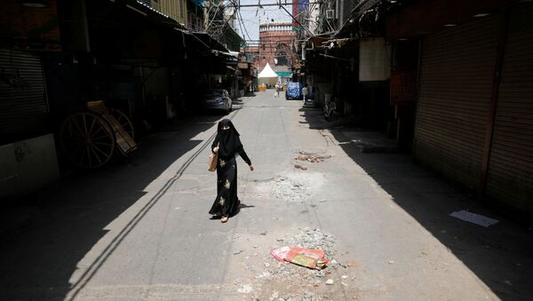 A woman walks on a deserted street during a nationwide lockdown to slow the spreading of the coronavirus disease (COVID-19) in the old quarters of Delhi, India, April 13, 2020 - Sputnik International