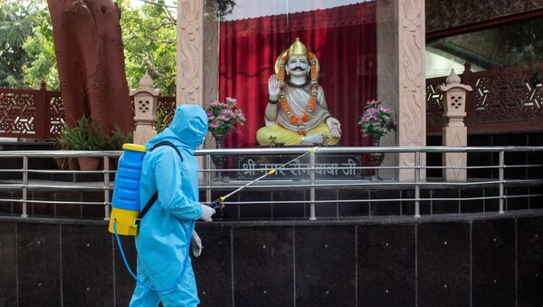 A health worker wearing protective gear sprays disinfectant at a crematorium to slow the spreading of the coronavirus disease (COVID-19), after India extended a nationwide lockdown to contain the disease, in New Delhi, India, April 14, 2020.  - Sputnik International