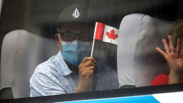 A man in a face mask waves a Canadian flag - Sputnik International