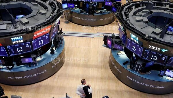 A trader puts on his jacket on the floor of the New York Stock Exchange (NYSE) as the building prepares to close indefinitely due to the coronavirus disease (COVID-19) outbreak in New York, U.S., March 20, 2020 - Sputnik International