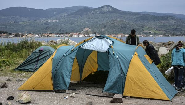 Migrants try to install a tent in the village of Petra on the northeastern Aegean island of Lesbos, Greece, Friday, 27 March 2020. Some 56 migrants who reached Lesbos in smugglers' boats from Turkey over the past few days have been quarantined in small tents in Petra for the past three days. Under public health measures adopted to hinder the spread of the new coronavirus, Greece places all people arriving from abroad in two-week quarantine. Lesbos' main migrant facility, near the village of Moria, is crammed with about 20,000 people even though it was built for 2,700. - Sputnik International