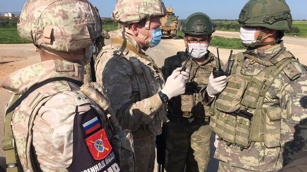 Soldiers of the Russian military police and the Turkish military during a joint patrol of the M-4 highway in Idlib province in Syria - Sputnik International