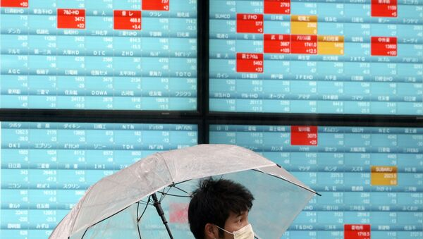 A man with a protective mask stands in the rain in front of an electronic stock board showing Japan's Nikkei 225 index at a securities firm in Tokyo Monday, April 13, 2020 - Sputnik International