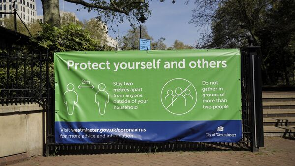A coronavirus guidelines banner is displayed by an entrance to Victoria Embankment Gardens in London, during the lockdown to try and stop the spread of coronavirus, Wednesday, 15 April 2020.  - Sputnik International
