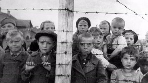 Staged photograph of Russian children at a formerly Finnish-run transfer camp in Petrozavodsk; photo taken by photographer Galina Sanko on 29 June 1944, one day after the Finns had left the area. The sign reads, in Finnish and Russian: Transfer camp. Entry to the camp and socializing through the fence are forbidden, violators will be shot - Sputnik International