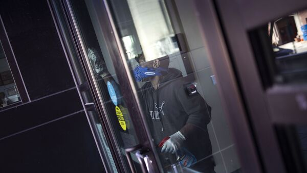 A worker disinfects the front doors of the School Without Walls High School in Washington - Sputnik International