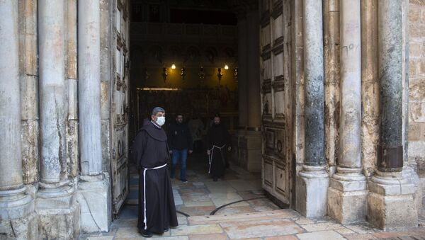 A Christian clergyman waits for the Easter Sunday Mass at the Church of the Holy Sepulchre, believed by many Christians to be the site of the crucifixion and burial of Jesus Christ, in Jerusalem's old city, Sunday, April 12, 2020.  - Sputnik International