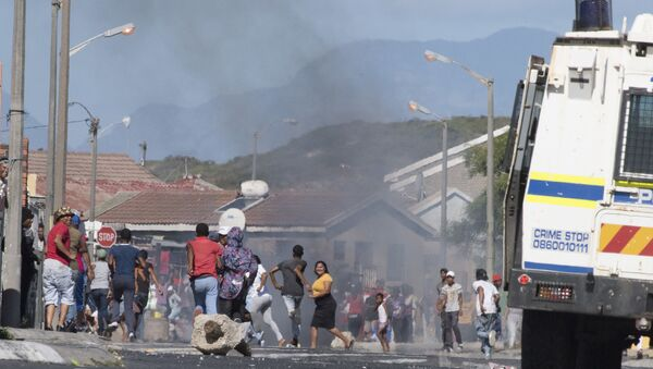 People run away as a South African Police Services armoured vehicle drives into a street during clashes with residents of Tafelsig, an impoverished suburb in Mitchells Plain, near Cape Town, on April 14, 2020, after some people in the community did not receive food parcels which were being handed out as part of the support for this community during the nation wide lockdown to curb the spread of the COVID-19 coronavirus.  - Sputnik International