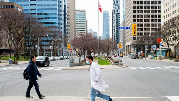 A health care worker runs across University Avenue from Mount Sinai Hospital to Toronto General Hospital as the number of the coronavirus disease (COVID-19) cases continues to grow in Toronto, Ontario, Canada April 17, 2020.  - Sputnik International